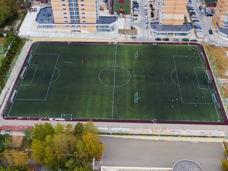 Aerial photography of a football field in the Park, city. people train on the field Banco de Imagens - 131974144