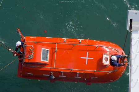 launching, lifting a lifeboat, two people leaned out of the hatch to release the hooks