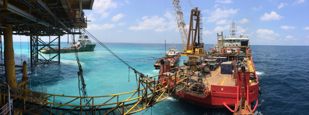 Accommodation vessel connects to platform via gangway during simultaneous operations with drilling rig.
