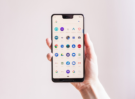 Hand holding Google Pixel 3 XL in front of plain background shows app list Редакционное