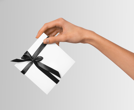 Isolated Woman Hands holding Holiday Present White Box with Dark Black Ribbon on a White Background