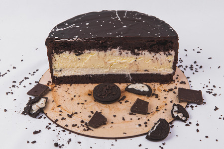 Chocolate cake with cheese filling decorated with biscuits on a white background