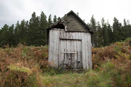 A disused bicycle in front of an old shed in Scotland