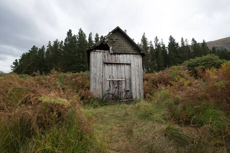 An old bicycle in front of a disused shed in Scotland