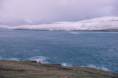 a lone red lighthouse in the faroe islands