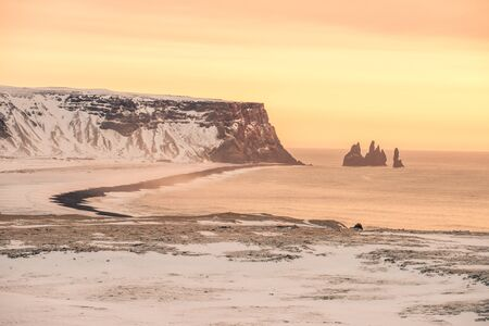 The sun sets on the snowy coast of Iceland Stock Photo