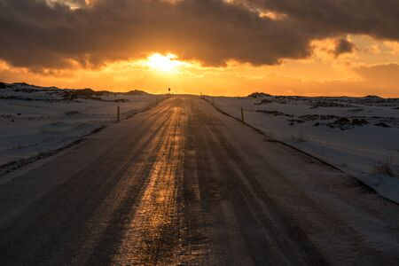 The sunset reflects on a road in Iceland Stock Photo