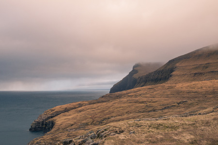 A field overlooking the cliffs in the faroe islands Stok Fotoğraf