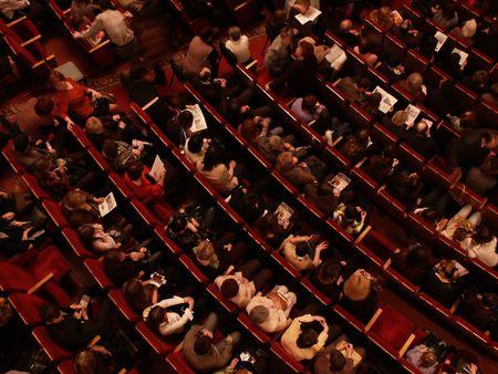 Teatro auditorium con alcune persone. Red sedie e piano.