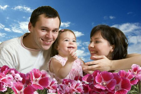 Happy family - mother, father and young cute daughter with flowers and skies as the background Stock Photo - 637815