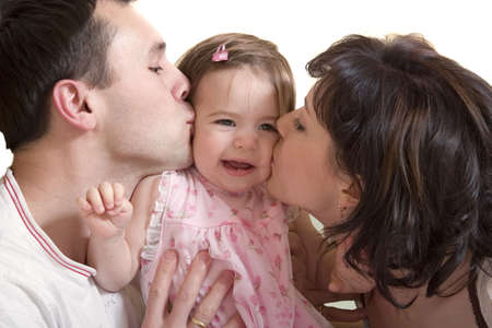Happy mother and father kissing their young cute daughter. Isolated on white background photo