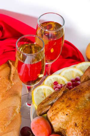 two glasses of wine with holiday dinner - roasted chicken or turkey with lemon, tomatoes, bread and cranberry photo