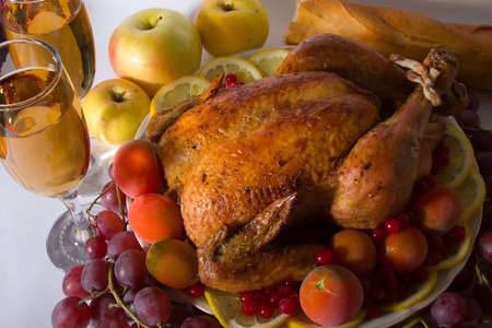 Roasted chicken or turkey garnished with lemon, cranberry, apples, tomatoes, bread and wine. photo