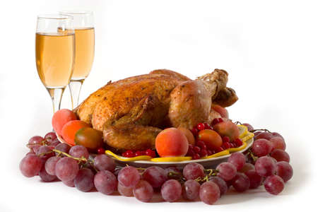 Roasted chicken or turkey garnished with lemon, cranberry, apples, tomatoes and wine. Isolated on white photo