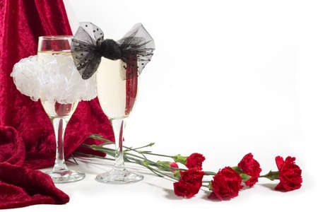 velure: two glasses of champagne with white and black bow knots, carnation and red velvet on white background with copyspace. Stock Photo