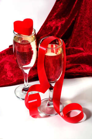 velure: two glasses of champagne with red twisted ribbon and plastic heart on white and red velvet background Stock Photo