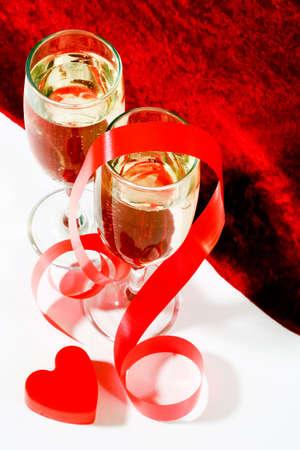 plastic heart: due vetri di champagne con il cuore torto rosso della plastica e del nastro sulla priorit� bassa bianca e rossa del velluto Archivio Fotografico
