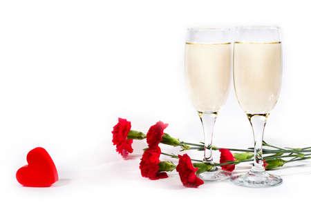 plastic heart: due bicchieri di champagne, garofano rosso di plastica e cuore a sfondo bianco con copyspace
