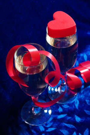 velure: two glasses of champagne, red twisted ribbon and plastic heart on the blue velvet