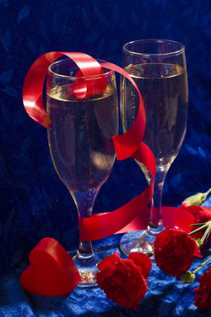 plastic heart: two glasses of champagne, red twisted ribbon, carnation and plastic heart on the blue velvet