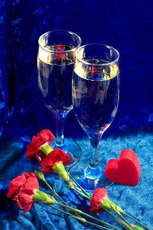 velure: two glasses of champagne, red plastic heart and carnation on the blue velvet