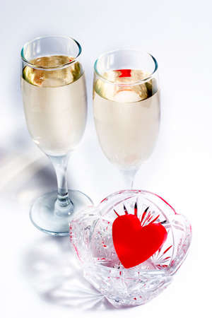 plastic heart: two glasses of champagne with red plastic heart in the crystal vase. White background