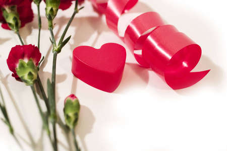 plastic heart: red plastic heart, twisted ribbon and red carnation with white background. With copyspace Stock Photo