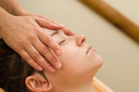therapeutic massage: young woman on the ayurvedic aromatherapy oil massage procedure
