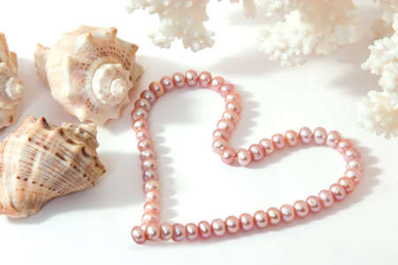 twiddle: Heart-shaped pearl beads with corals and shells on white background