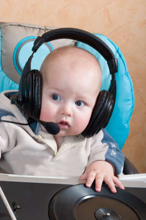 baby with headphones and microphone playing with turntable photo