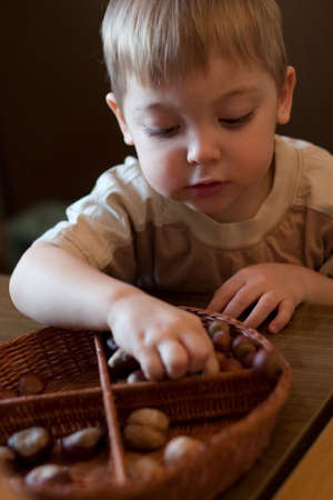 little boy playing with basket and nuts in the kindergarten Stock Photo - 761433