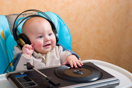 baby with headphones playing with turntable photo