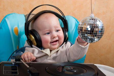 auriculares dj: beb� con auriculares jugando con plataforma giratoria bola de discoteca y