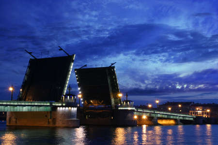Open drawbridge over Neva river in St. Petersburg at the late evening photo