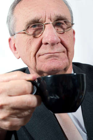 focal point: an old businessman have a coffee break. Focal point is on the face