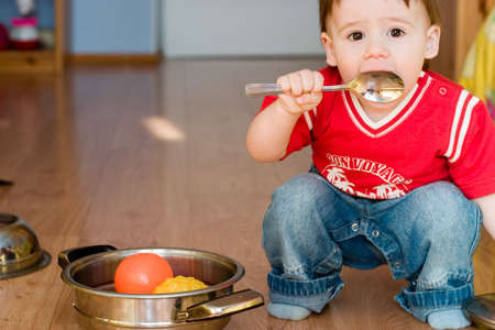 Cute little boy sitting on the floor with spoon in his hand Stock Photo - 818212