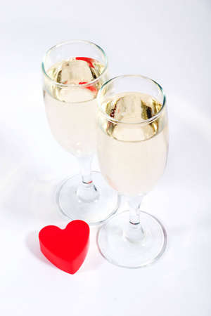 plastic heart: two glasses of champagne and red plastic heart Stock Photo