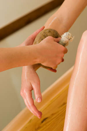 ayurvedic oil massage procedure with pouch of rice and spices photo