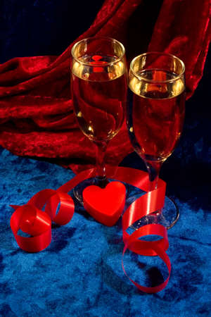 velure: two glasses of champagne, red twisted ribbon, and plastic heart on the blue velvet
