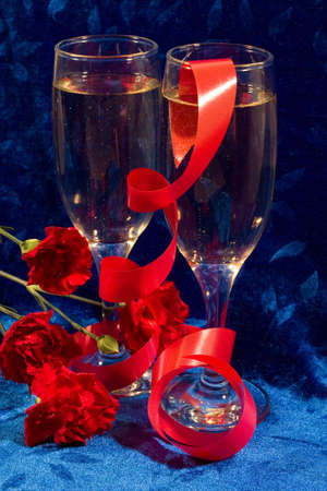 velure: two glasses of champagne, red twisted ribbon and carnations on the blue velvet