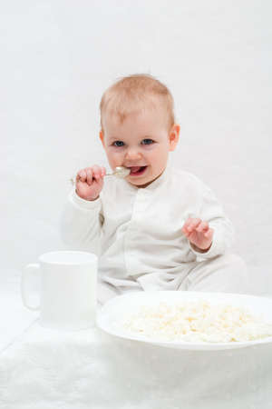curd: cute little girl sitting on white blanket with spoon in her hands. There are white plate with curd and white cup in front of her.