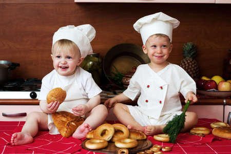 two little boys in the cook costumes at the kitchen sitting on the table Stock Photo - 917672