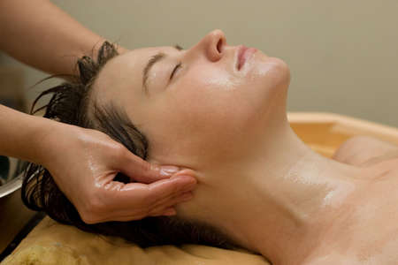 young woman on the ayurvedic aromatherapy oil massage procedure photo