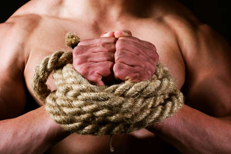 rope-bounded hands of young male athlete. Concept for freedom, struggle etc. photo