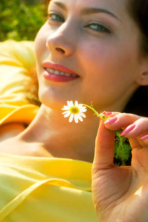 beautiful girl with camomile lying in the rays of sun. Soft-focused, focal point is on flower Stock Photo - 1477715