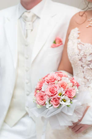 just married - young couple in wedding wear with bouquet of roses. Low DOF, focal point is on the flowers Stock Photo - 1678086