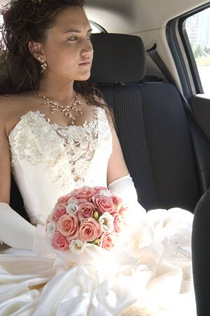 young bride in wedding wear with bouquet of roses sitting in the car photo