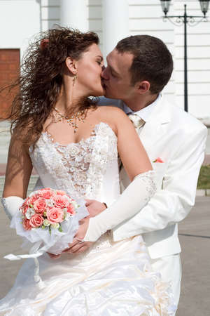 just married - kiss of young couple in wedding wear with bouquet of roses Stock Photo - 1841947