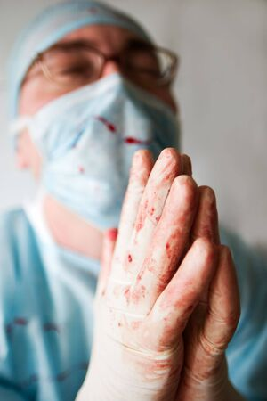 focal point: surgeon, bespattered with blood, praying for patient life. Low DOF, focal point is on hands Stock Photo