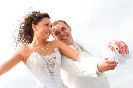 결혼식: young couple in wedding wear with bouquet of roses. 스톡 콘텐츠